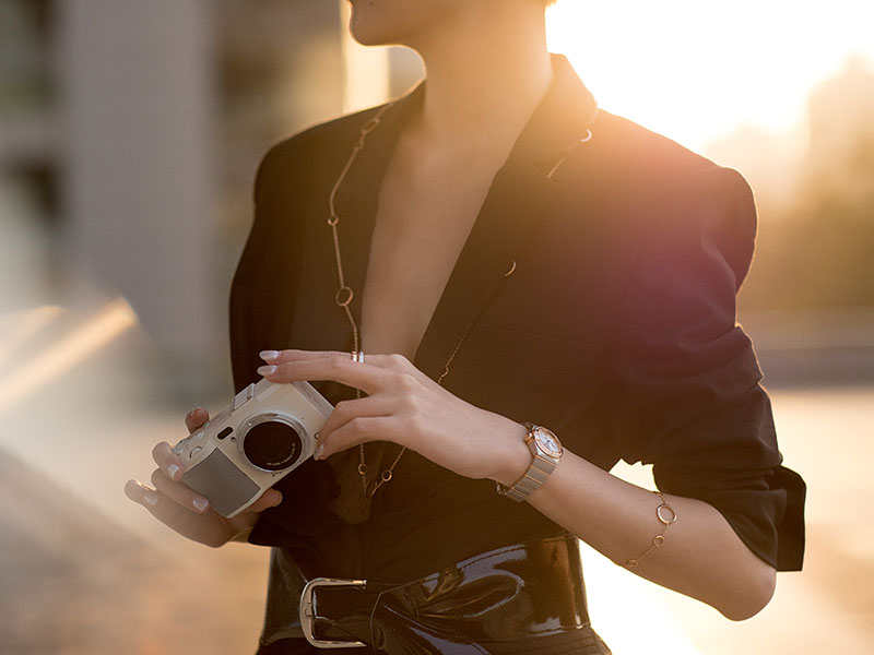Woman holding a camera wearing a Constellation watch