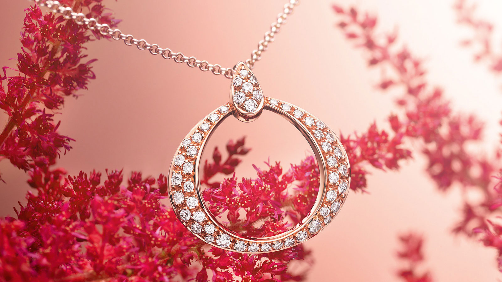 Elegant closeup of an Omega Dewdrop pendant in rose gold and encrusted with diamonds