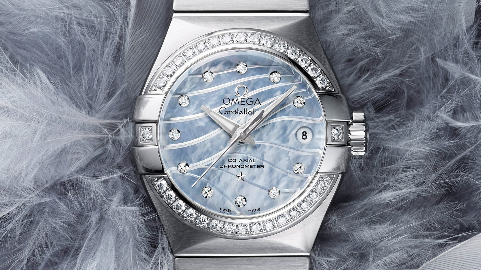 Closeup view of a Constellation watch for women with a stainless steel and diamond encrusted watch case and a blue mother-of-pearl dial