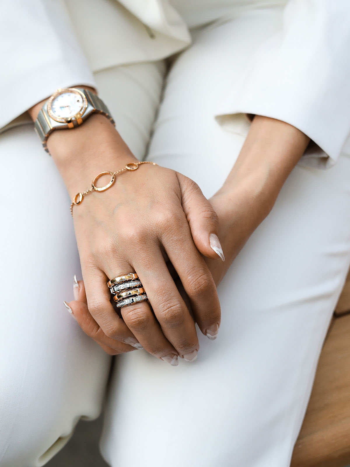 Close-up of model @CATCHERINTHESTYLE wearing and Omega Constellation bracelet and rings