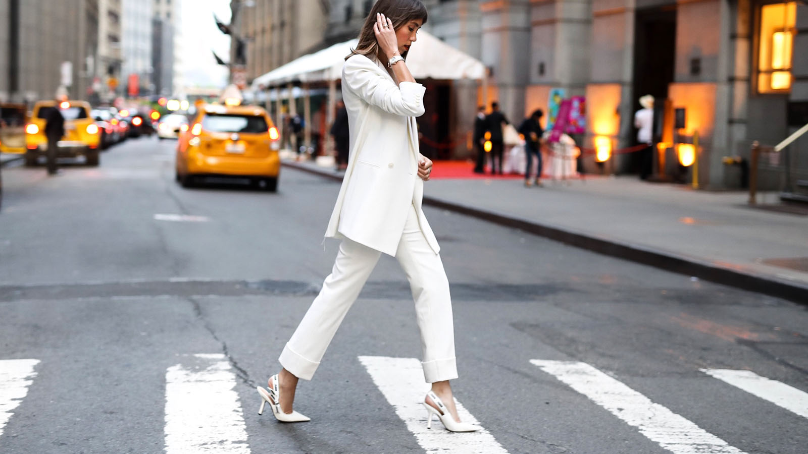 Model @CATCHERINTHESTYLE crosses the street while wearing an Omega Constellation watch