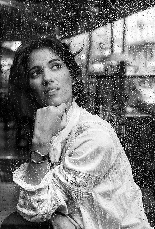 Woman wearing a De Ville Trésor watch looking through a window full of rain spots