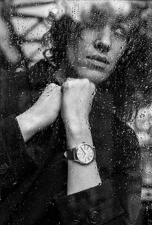 Model wearing a De Ville Trésor watch looking through a window full of rain spots