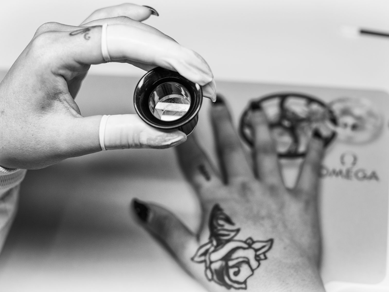 Hands with gloves holding a magnifying glass