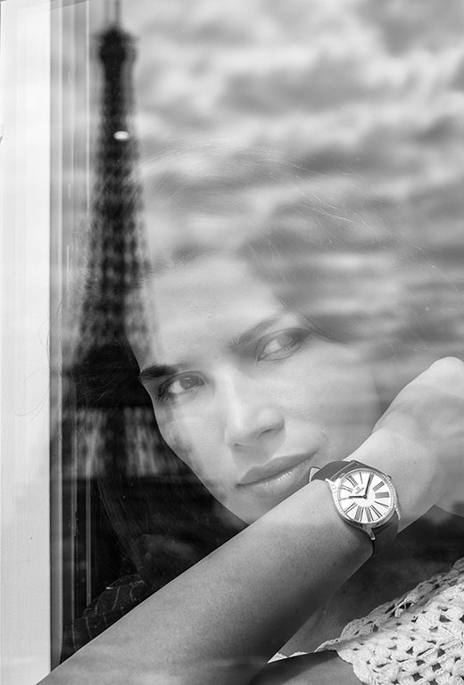 Model wearing a De Ville Trésor watch looking through a window