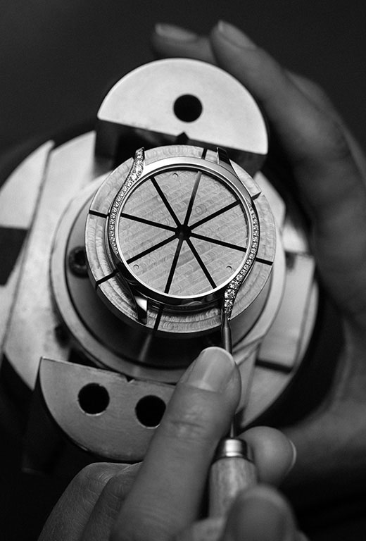 Watchmaker placing diamonds on the side of the Omega Trésor