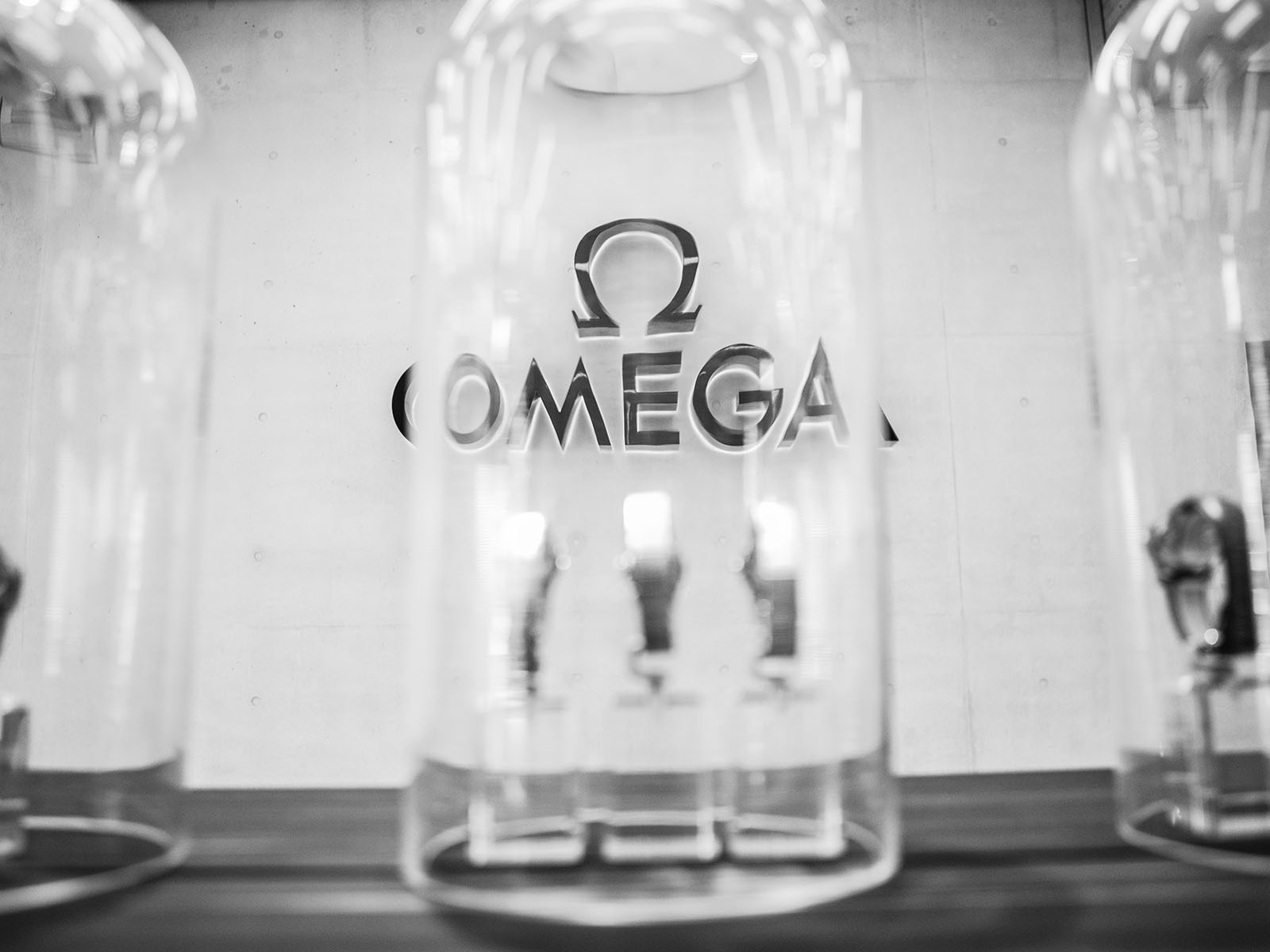 omega logo seen through a bell jar