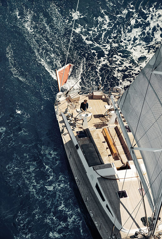 A birds-eye view of Eddie Redmayne at the helm of a yacht under full sail.