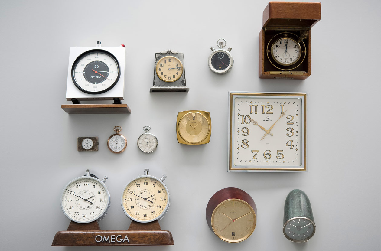 14 Omega clocks, chronometers and pocket watches of different color and shapes hung on a wall