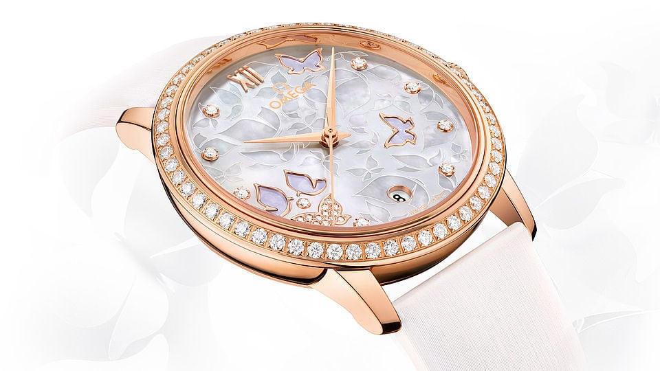 Closeup of a Prestige Butterfly watch dial engraved with butterflies with a rose gold diamond encrusted case