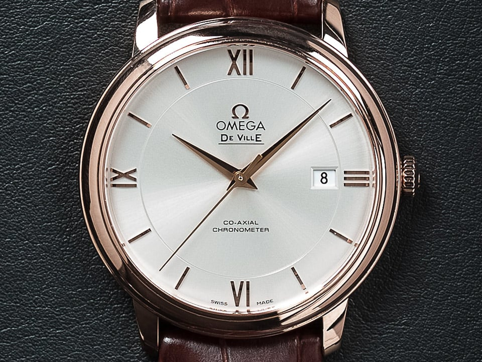 Closeup of a Prestige watch dial with a classic white dial and roman numerals