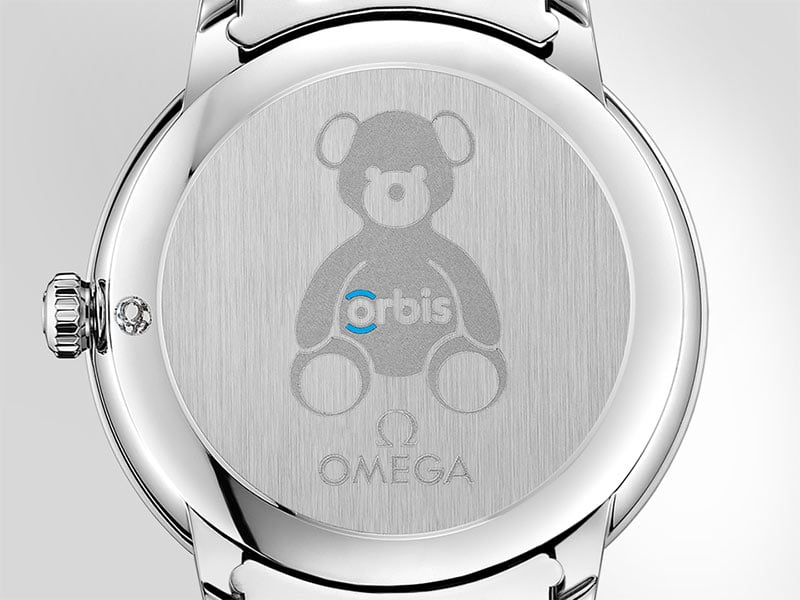 Caseback of an Orbis watch engraved with a teddy bear