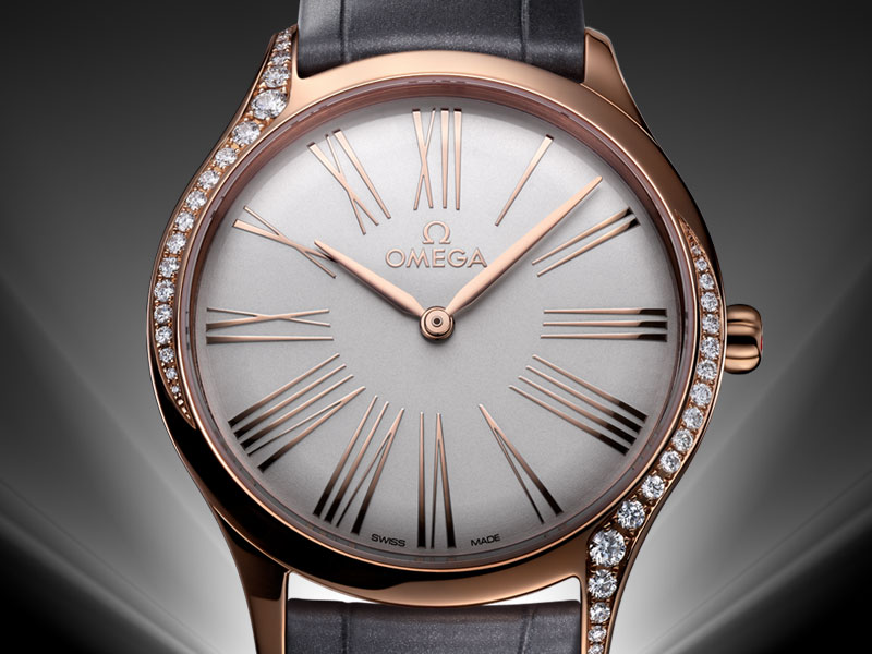 De Ville Trésor watch in rose gold with large roman numbers, elegantly encrusted with diamonds that curve around each side of the case