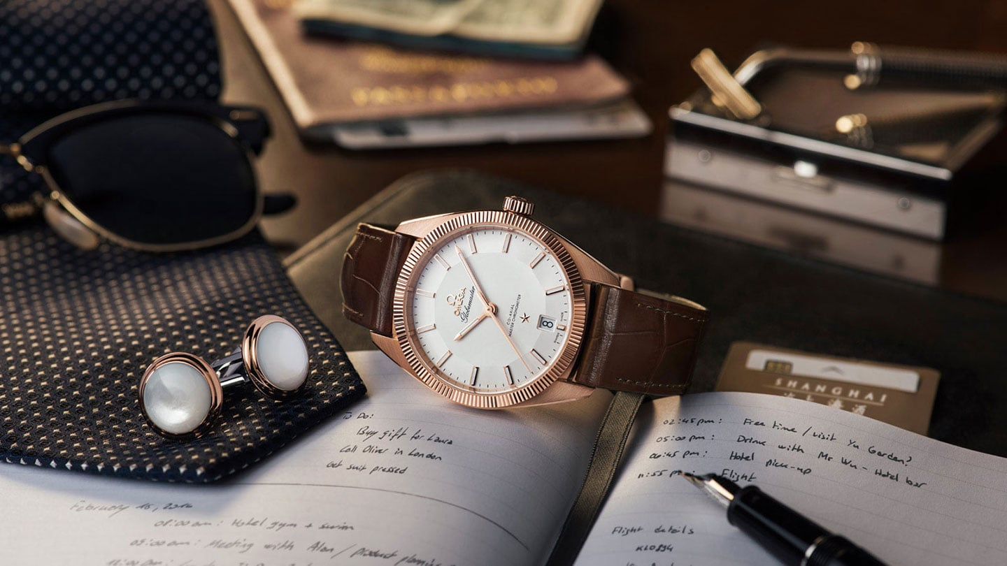 Contextual view of a Globemaster watch with a rose gold case and brown leather strap posed on a desk next to Omega cufflinks