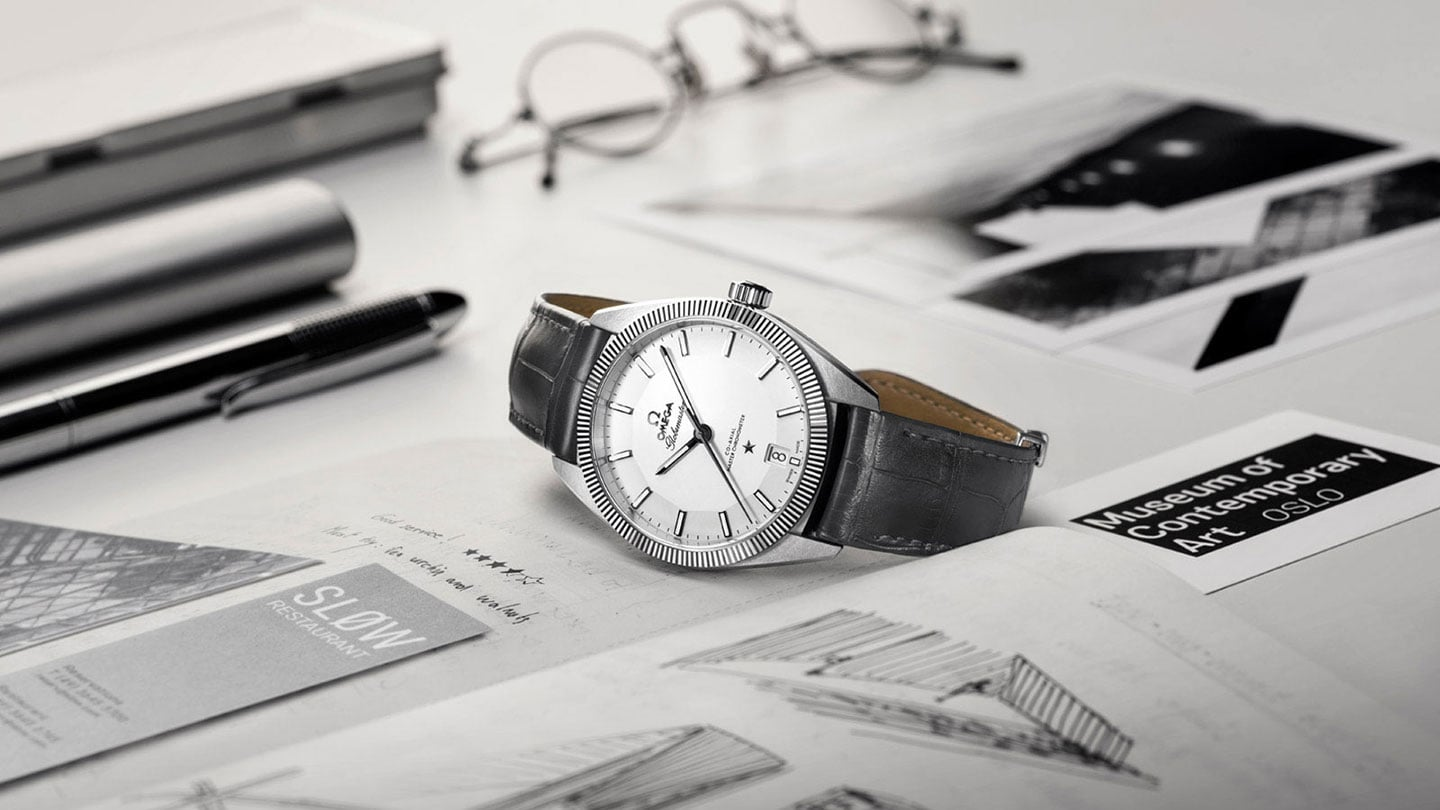 Contextual view of a Globemaster watch with a stainless steel case and grey leather strap posed on a desk
