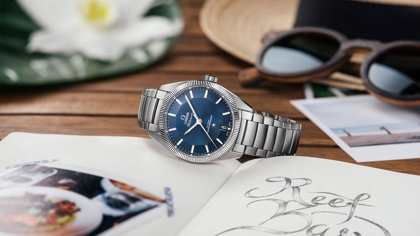 Contextual view of a Globemaster watch with a stainless steel bracelet and blue pie-pan dial pose on a wooden table