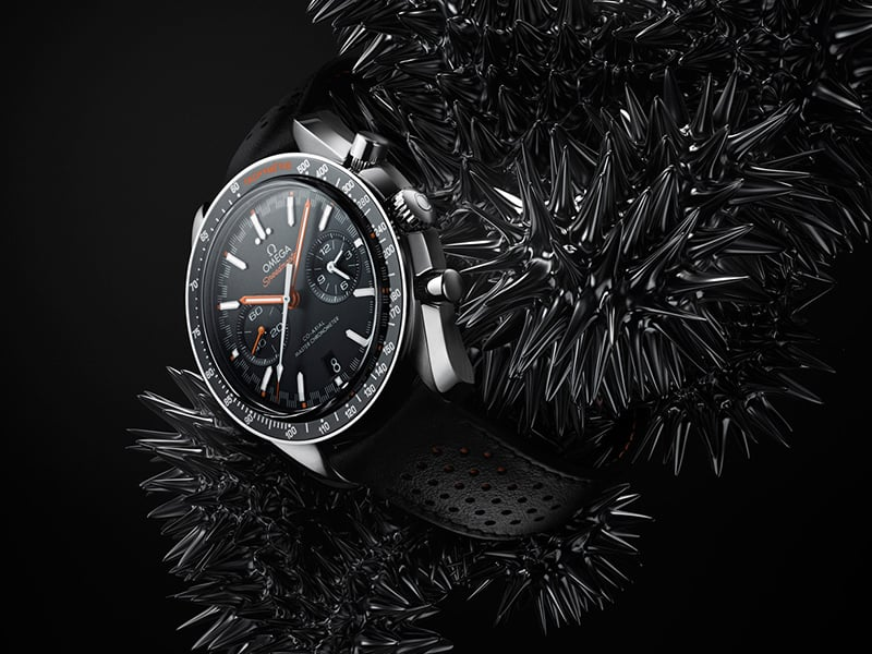 Black Omega Speedmaster watch strapped on a mass of liquid metal balls with rounded spikes