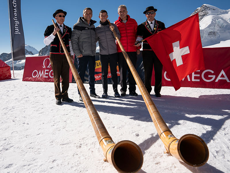 Rory McIlroy and Raynald Aeschlimann pose with traditional Swiss instruments