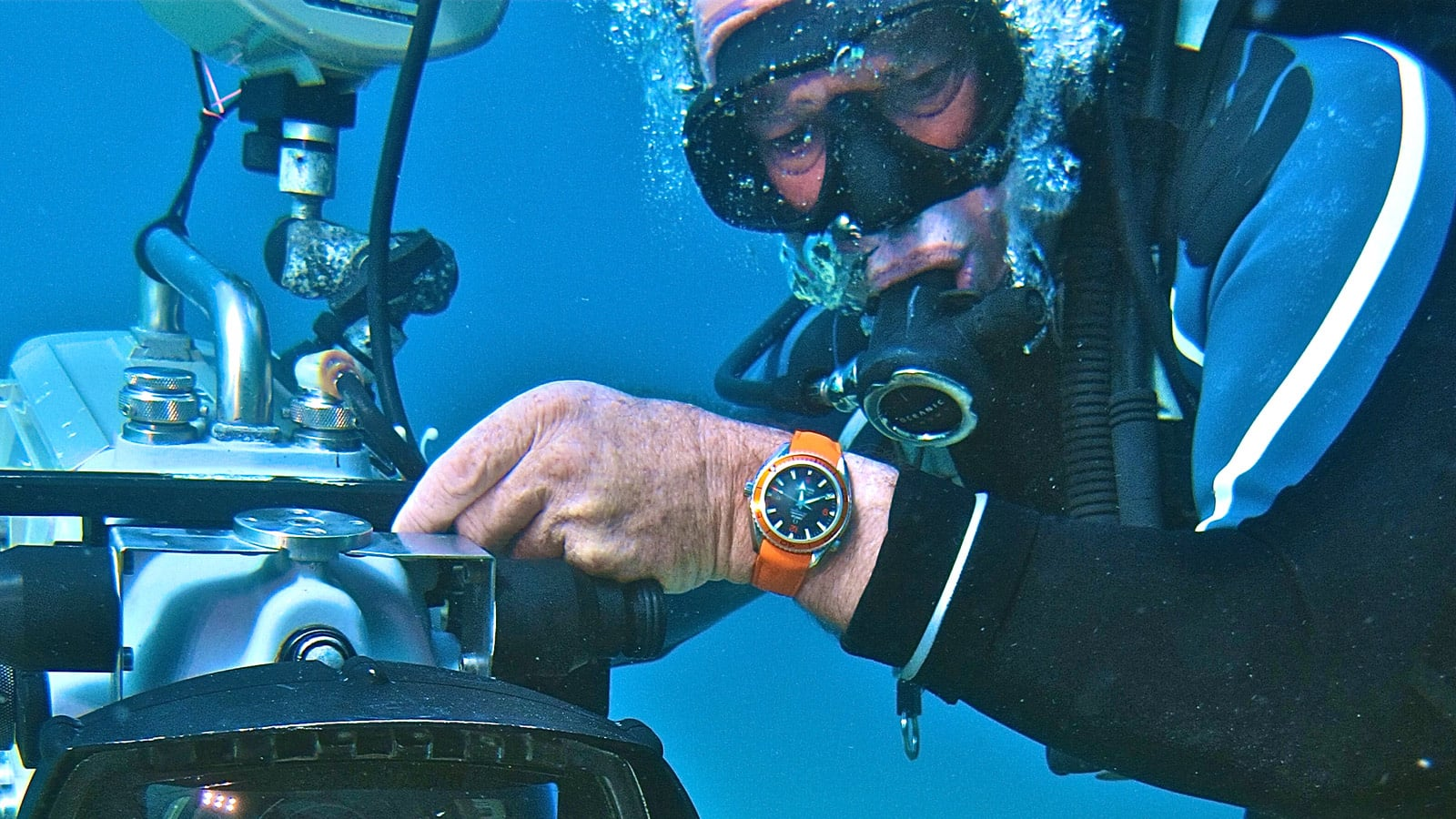 Close view of a cameraman underwater with his Omega watch