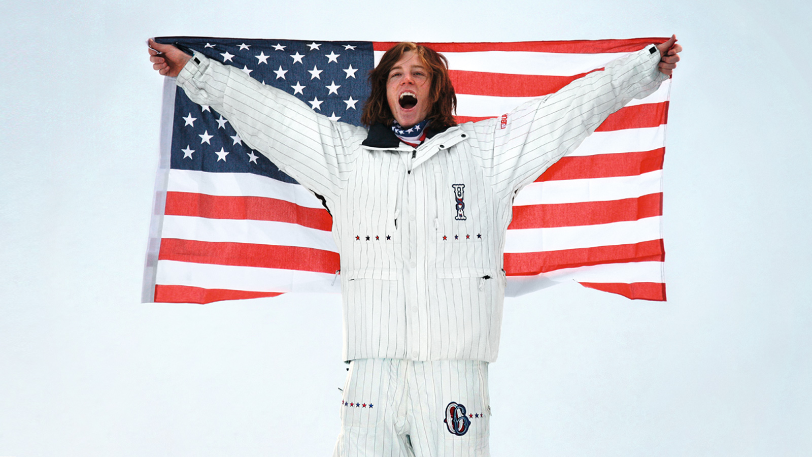 Snowboarder Shaun White hold an american flag and celebrates on the podium of 2006 Turin Winter Olympics