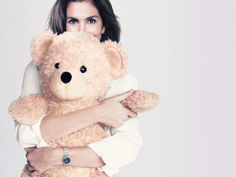 Cindy Crawford holding a teddy bear in support for Orbis International