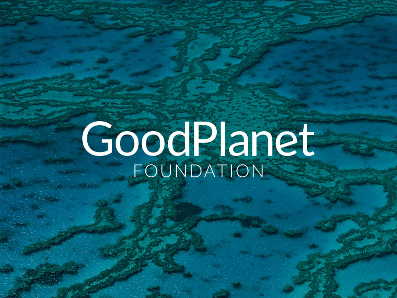View from the sky of an atoll with open lagoon and in the center the white text GOODPLANET FOUNDATION