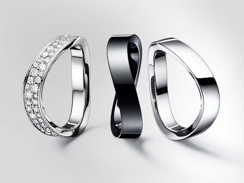 Three Omega Aqua Swing rings in gold, black ceramic and white gold encrusted with diamonds
