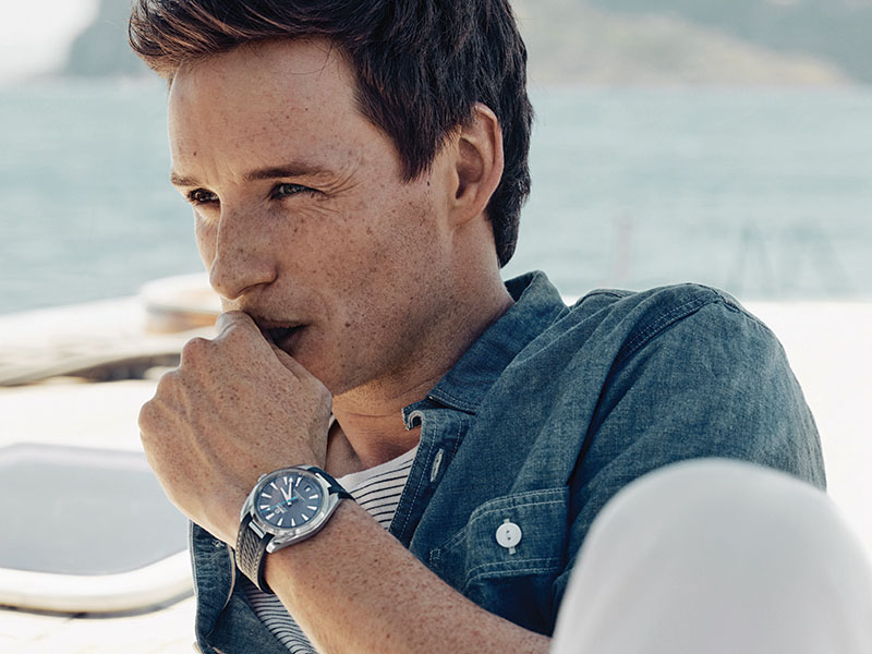 Eddie Redmayne, in a relaxed pose and wearing a Seamaster Aqua Terra, scans the horizon.