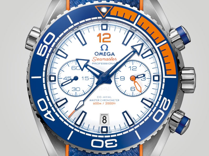 """Close view of the face of the """"Michael Phelps"""" Seamaster watch and its orange and blue bezel"""