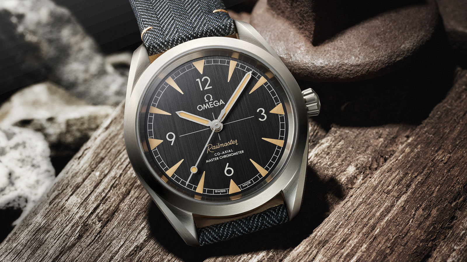 Close view of the case of the Seamaster Railmaster watch with coated nylon fabric strap on a wooden support