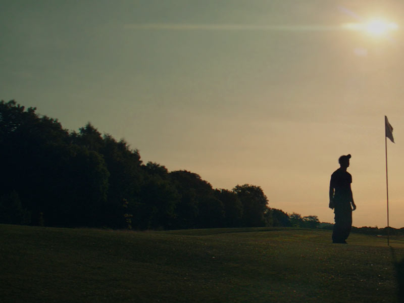 Golf players, watching the sunset on the golf course.