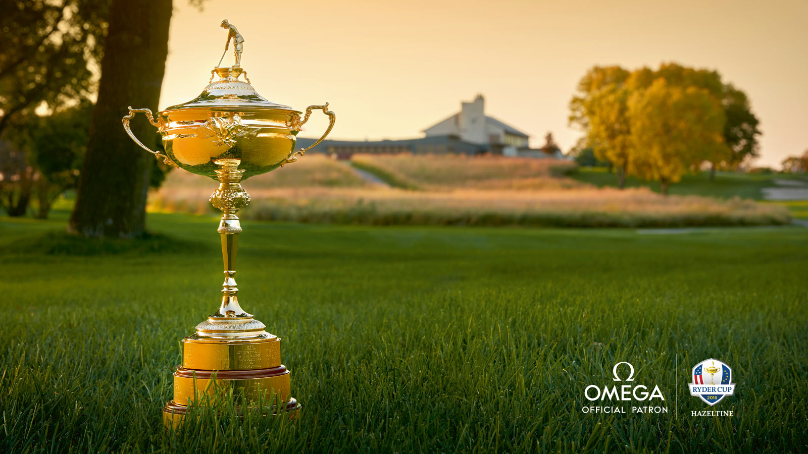 The cup of the Ryder Cup golf competition, standing on grass with fields and trees in the background.