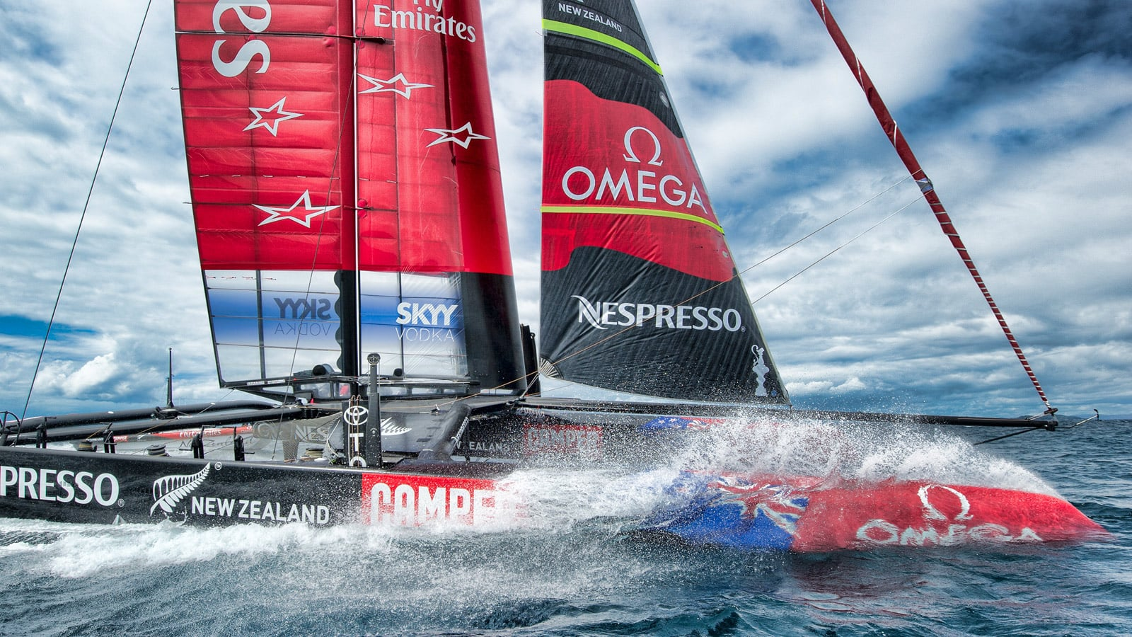 The catamaran of the Emirates Team New Zealand braving a wave in the middle of the sea