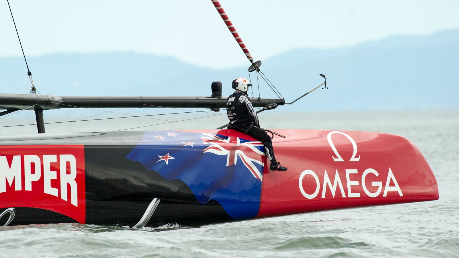 A member of the Emirates Team New Zealand, sitting at the front of the catamaran, looking at the horizon