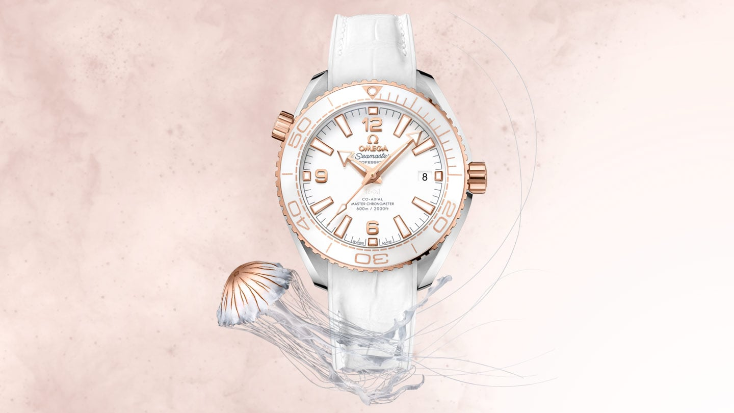 White Planet Ocean 600M Omega Co-Axial Master Chronometer Watch with Sedna gold case and indexes on a white face, presented with a jellyfish in the same colors