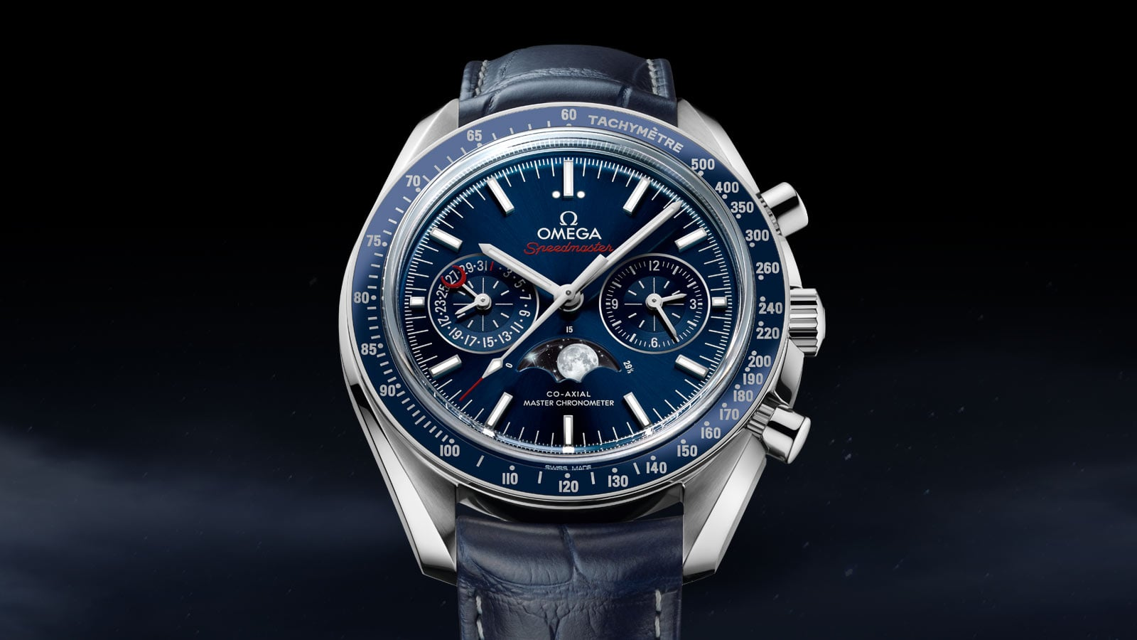 Close-up view of the Omega MOONWATCH MOONPHASE with blue sun-brushed dial and blue leather strap