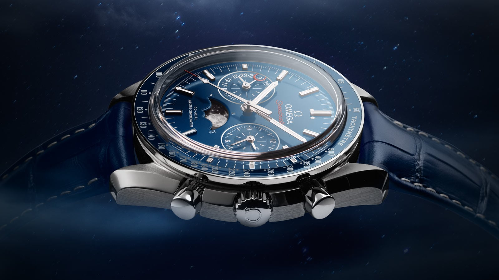 Side shot of the Omega MOONWATCH MOONPHASE steel case on blue bracelet