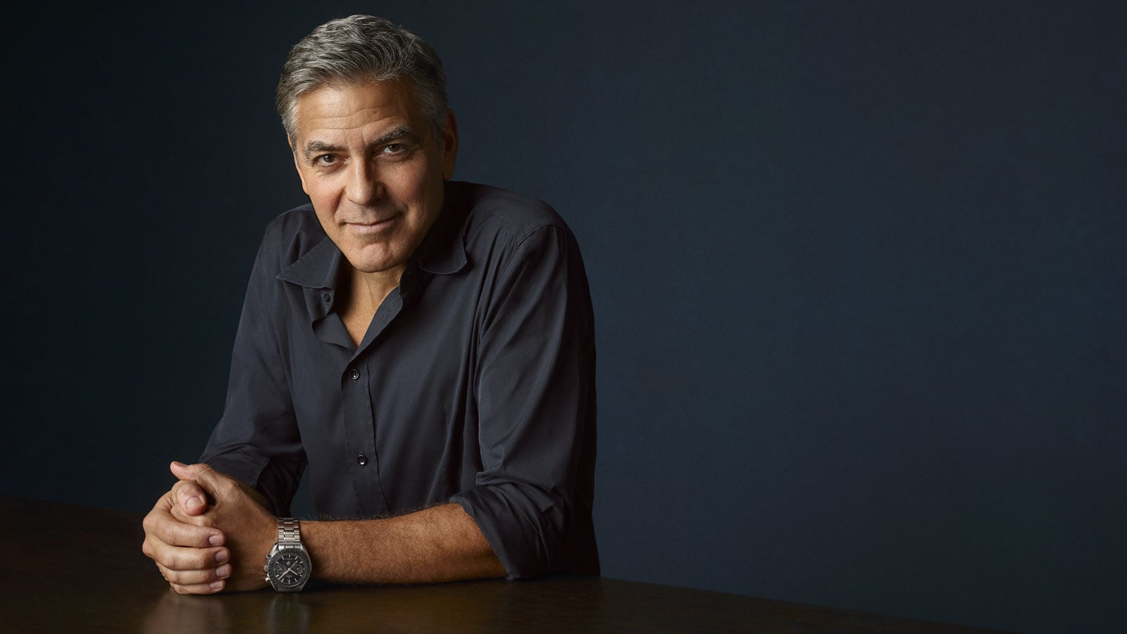 George Clooney looking at the camera while having his hands resting on a table