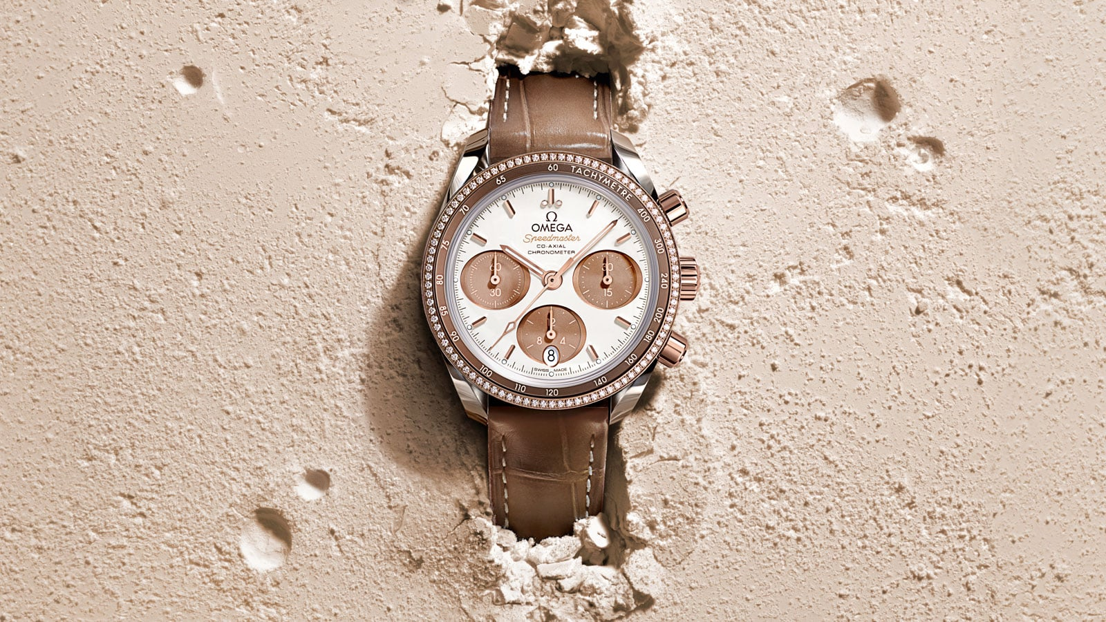 Contextual view of a Speedmaster 38mm watch with a steel and Sedna gold case and leather bracelet placed in sand