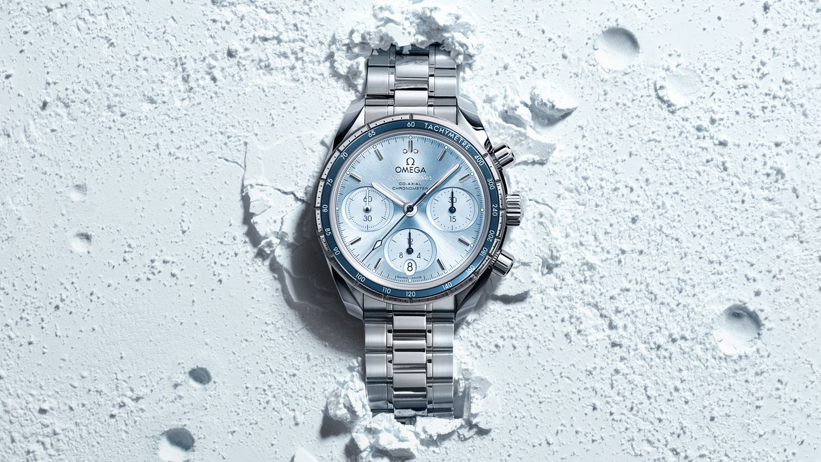 Contextual view of a Speedmaster 38mm watch with a light blue dial and steel bracelet placed in sand
