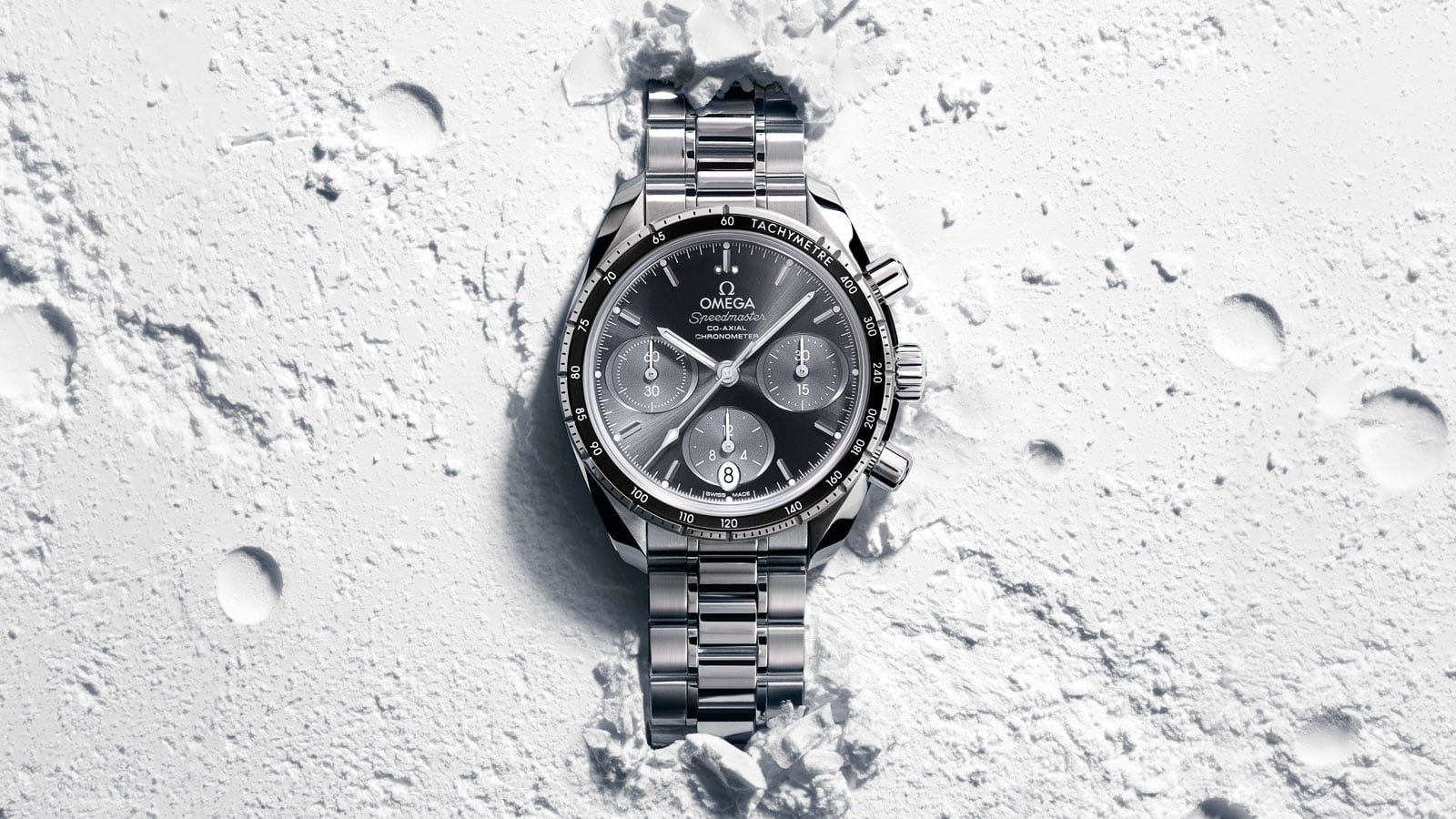 Contextual view of a Speedmaster 38mm watch with a white dial and stainless steel bracelet placed in sand