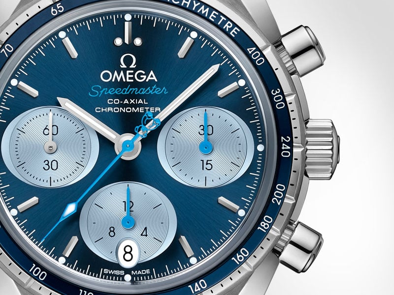 "The blue dial of the Speedmaster 38mm ""Orbis"". The hands are rhodium-plated just like the sun-brushed dial. The blue central second hand features an Orbis teddy bear as counter-weight."