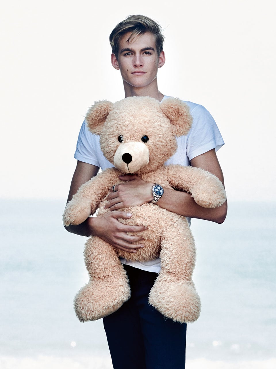 "Presley Gerber, holding a special Orbis teddy bear and wearing a Speedmaster 38mm ""Orbis"" watch"