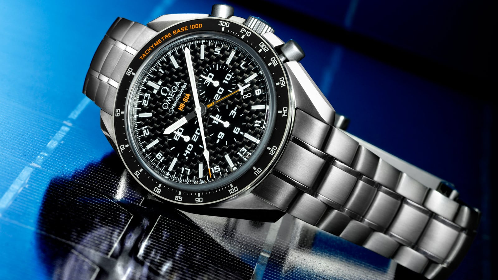 Omega SPEEDMASTER HB-SIA GMT CHRONOGRAPH with titanium bracelet and case a black bezel and a black carbon fiber dial placed on a on a photovoltaic panel