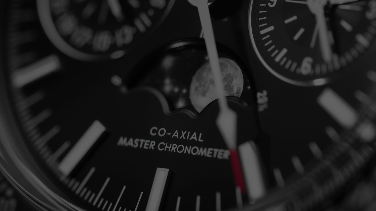 Blurred close-up view of an Omega Moonwatch Moonphase with a black dial