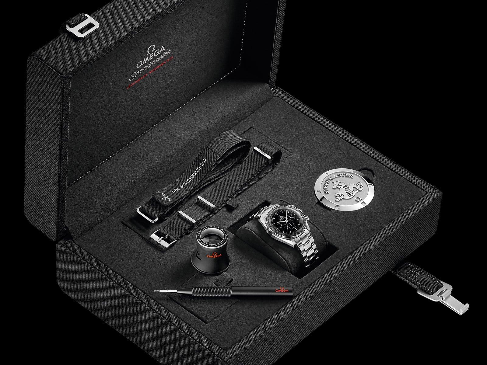 Special presentation box of the SPEEDMASTER PROFESSIONAL MOONWATCH with two additional straps plus a tool to change bracelets and the instructions along with a Speedmaster loupe, a metal plate and a book about the Speedmaster