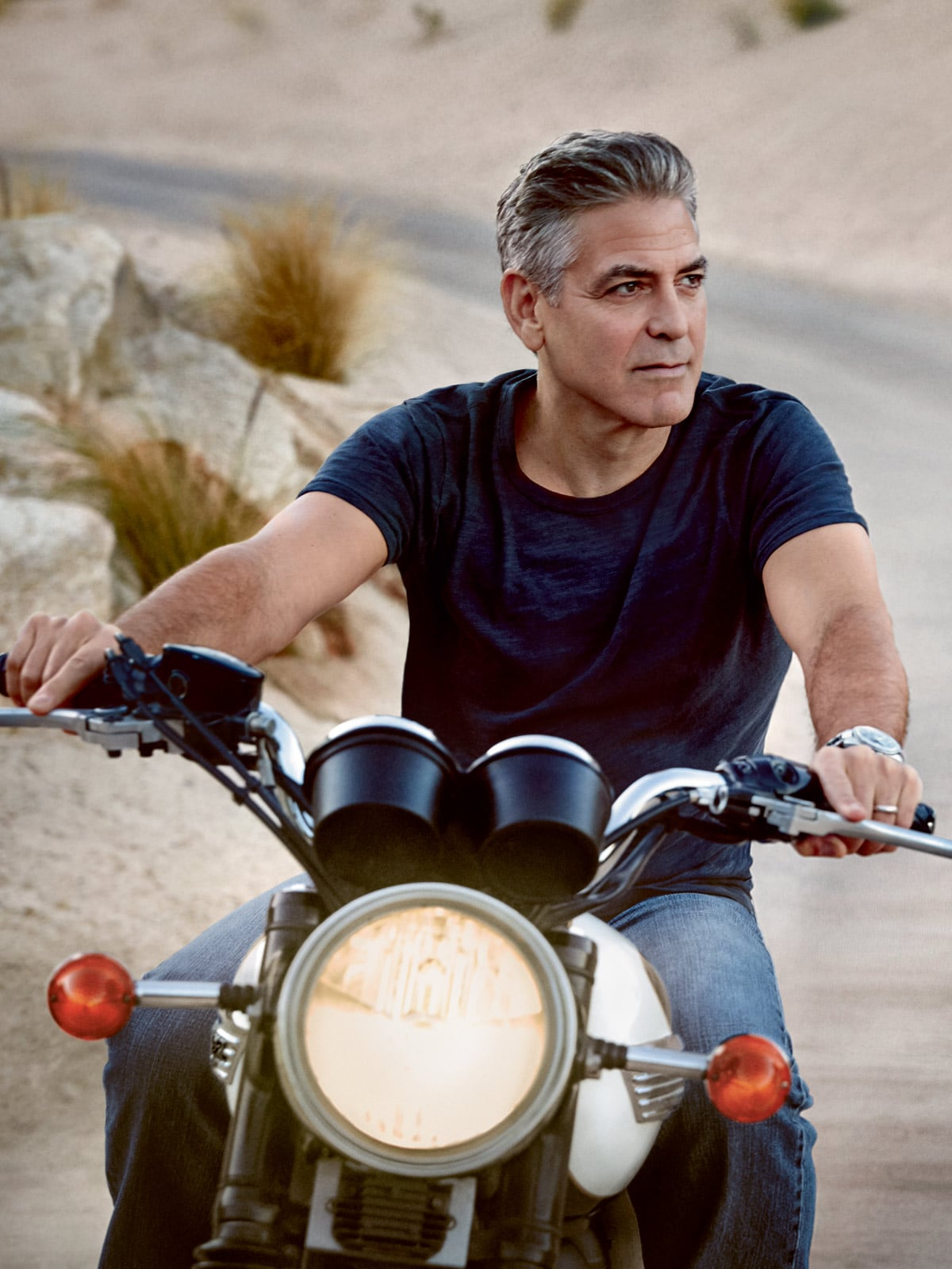 George Clooney riding a motorcycle while wearing the Omega Speedmaster '57 watch