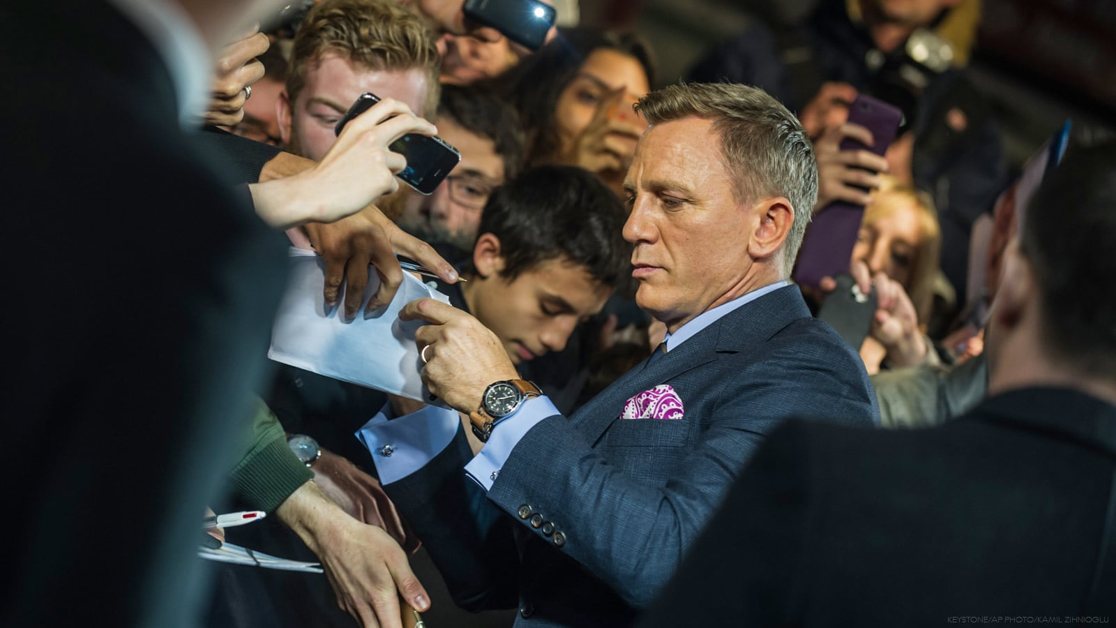 Picture of Daniel Craig signing autographs in a crowd of fans