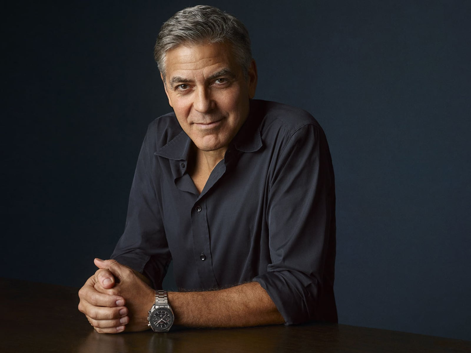 George Clooney leaning on a table