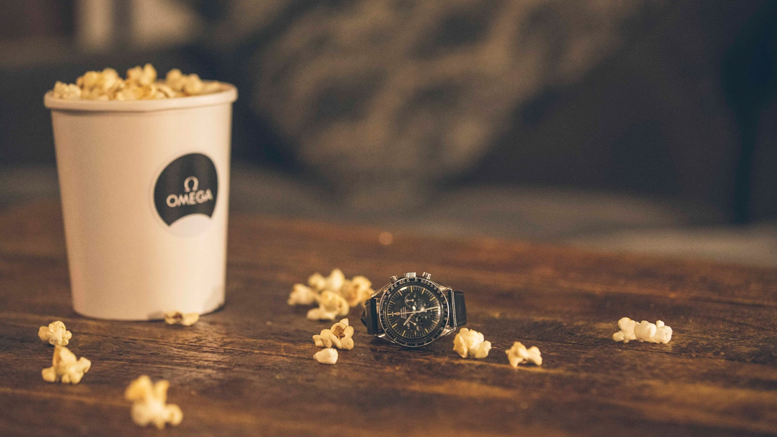 Box of popcorn and a black omega watch on a table